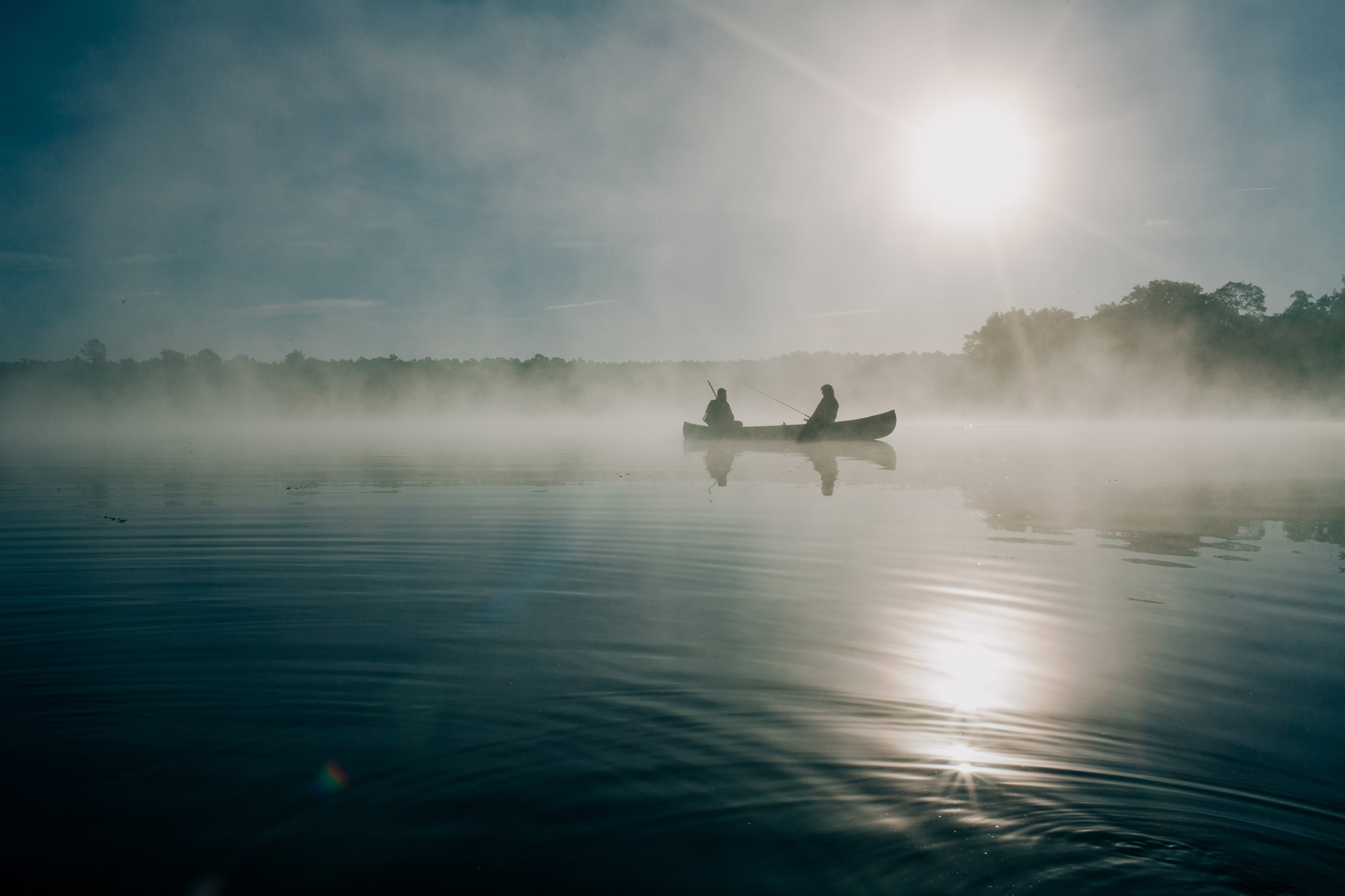 Two people in canoe on lake - via Unsplash Ravi Pinisetti